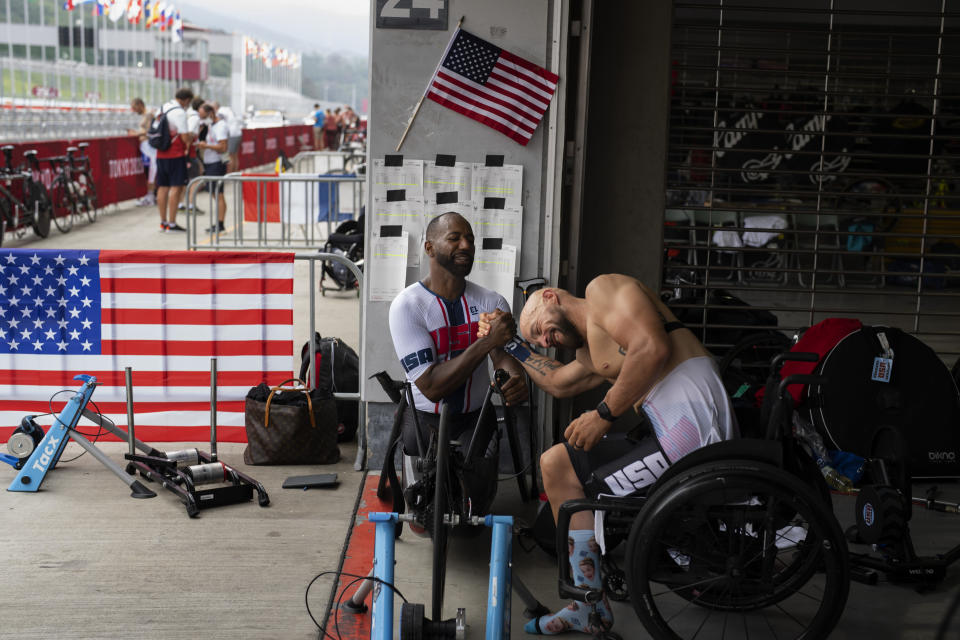 Tom Davis, shakes hands with Freddie De Los Santos after winning at Men's H4 Time Trial at the Fuji International Speedway at the Tokyo 2020 Paralympics, Tuesday, Aug. 31, 2021, in Tokyo, Japan. (AP Photo/Emilio Morenatti)