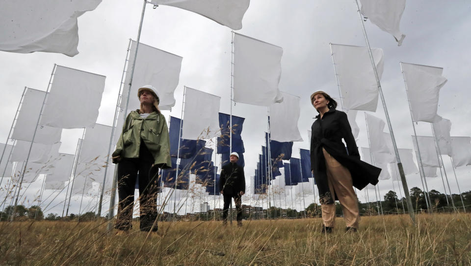 Nurse Angela Helleur, right, is guided through Luke Jerram's In Memoriam art installation that was erected outside the Queen Elizabeth Hospital on Woolwich Common in London, Saturday, Aug. 29, 2020. It has been created as a memorial to those lost in the Covid-19 pandemic as well a tribute to the NHS and care-workers. Created from bed sheets, In Memoriam is intended to be an evocative symbol of local, national and international solidarity, presented as a space for reflection, remembrance, and recognition.(AP Photo/Frank Augstein)