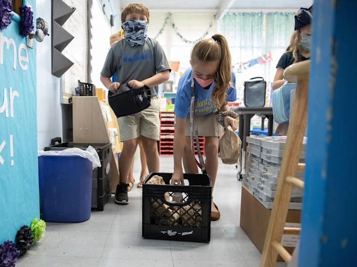 Children retrieve bagged lunches in their classroom at Columbia Elementary School on August 25, 2020 in Columbia, Mississippi.