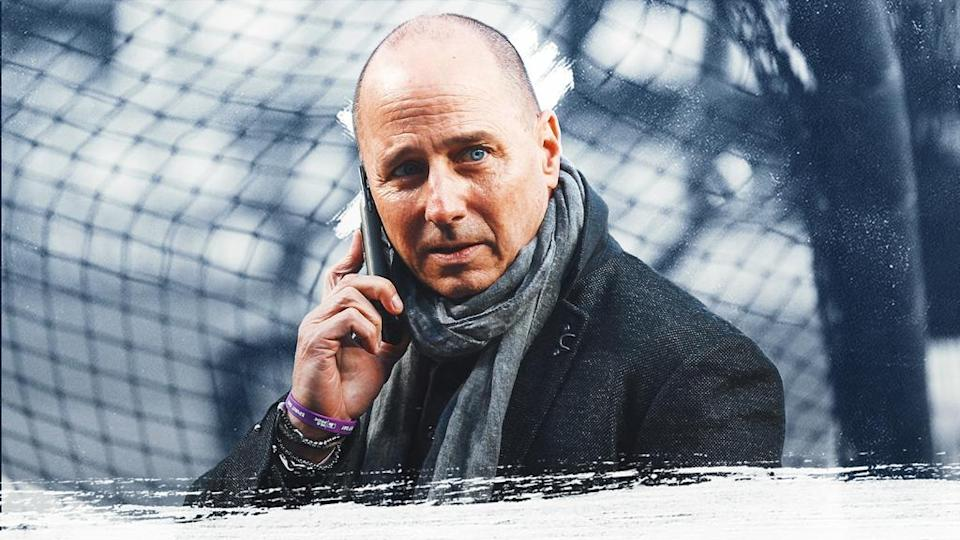 Yankees GM Brian Cashman treated image, on phone wearing coat with blue/grey background