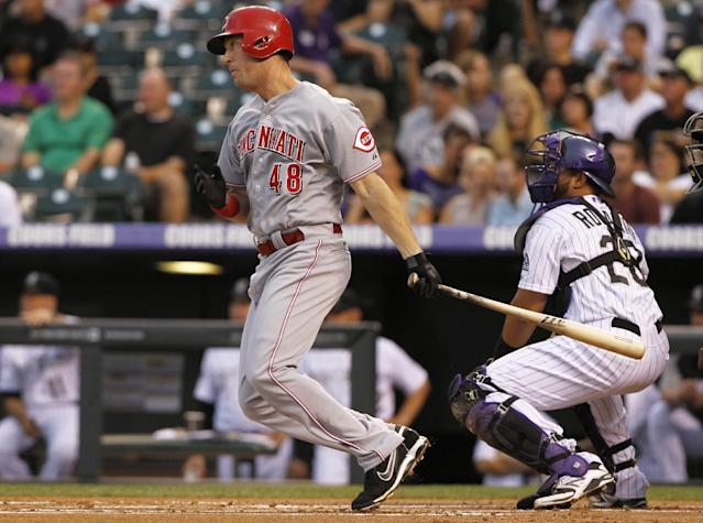 Cincinnati Reds' Ryan Ludwick, left, follows the flight of his single with Colorado Rockies catcher Wilin Rosario in the first inning of a baseball game in Denver on Saturday, Aug. 31, 2013. (AP Photo/David Zalubowski)