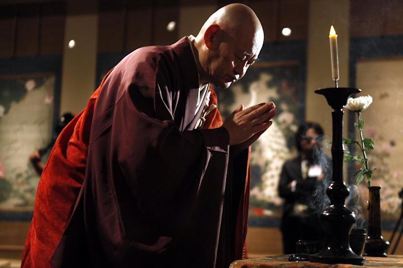 Rev. Raitei Arima, a monk from Shokokuji Monastery in Japan, performs a blessing ceremony over a 30-scroll set of paintings from the 1700s, considered a cultural treasure of Japan, Monday, March 26, 2012, at The National Gallery of Art in Washington. The museum displays the bird-and-flower paintings that date back to 1716 to mark the centennial of Japan's gift of 3,000 cherry trees to the nation's capital. (AP Photo/Jacquelyn Martin)