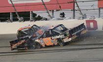 Kris Wright (02) and Codie Rohrbaugh (9) crash in Turn 2 during the NASCAR Truck Series auto race at Darlington Raceway, Friday, May 7, 2021, in Darlington, S.C. (AP Photo/Terry Renna)