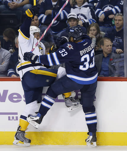 Nashville Predators' Victor Bartley (64) and Winnipeg Jets' Dustin Byfuglien (33) collide during the first period of an NHL hockey game Tuesday, Nov. 4, 2014, in Winnipeg, Manitoba. (AP Photo/The Canadian Press, John Woods)