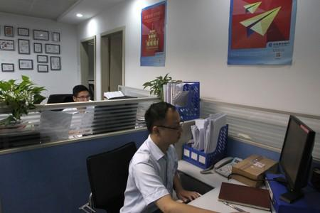 Bank employees, at the small business lending department of CCB, work in front of their computers at the bank's Dongguan branch office