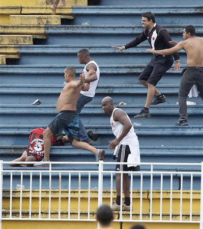 Vasco da Gama soccer fans beat up an Atletico Paranaense fan during their Brazilian championship match in Joinville in Santa Catarina state December 8, 2013. REUTERS/Carlos Moraes