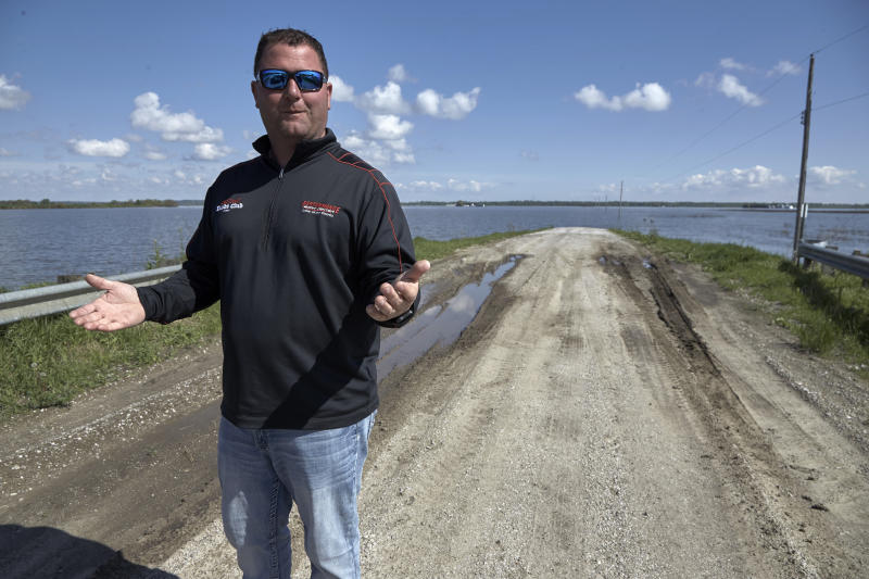 In this May 10, 2019 photo, Brett Adams gestures as he stands where the road to his flooded farm disappears under flood waters, with the farm buildings seen in the background, in Peru, Neb. Adams had thousands of acres under water, about 80 percent of his land, this year. The water split open his grain bins and submerged his parents' house and other buildings when the levee protecting the farm broke. (AP Photo/Nati Harnik)