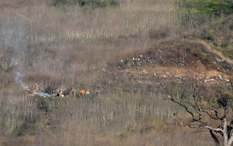 Members of LA County Fire and LA County corners begin the task of removing bodies from the hillside  - Credit: USA Today