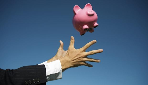 Pair of male hands in suit and barrel cuffs reaches out to catch pink piggy bank falling in blue sky