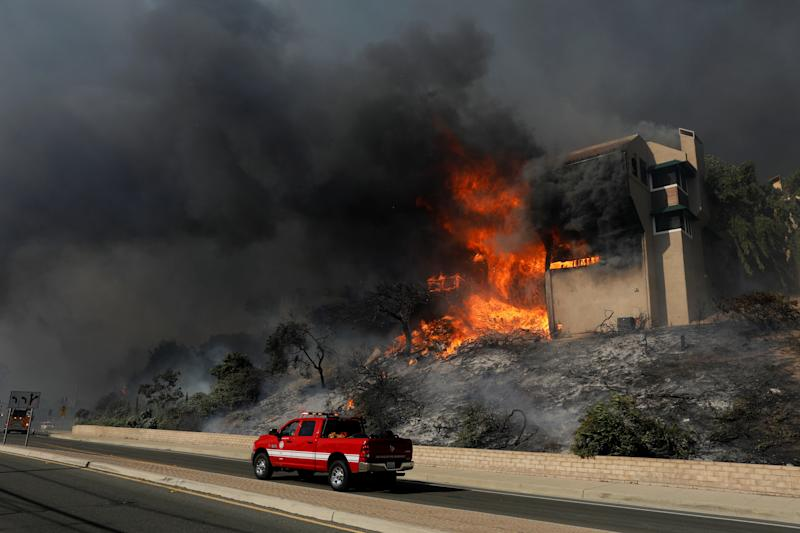 A fire officials drives past a burning home in Ventura, California, on Tuesday. (Mike Blake / Reuters)