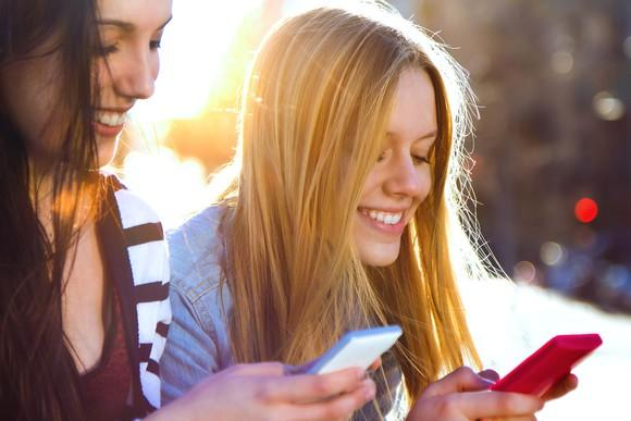 Two young women using their smartphones.