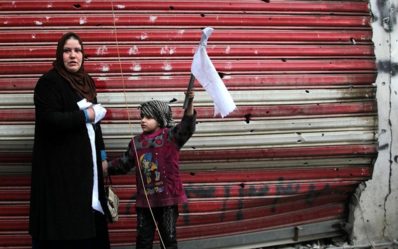 An Iraqi woman and her daughter stand on a street holding white flags as Iraqi security forces secure Mosul's Al-Dawasa neighbourhood on March 13 - Credit: AFP