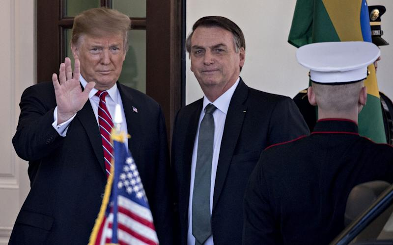 U.S. President Donald Trump, left, waves while standing with Jair Bolsonaro, Brazil's president, at the West Wing of the White House in Washington, D.C., U.S., on Tuesday, March 19, 2019. - Bloomberg