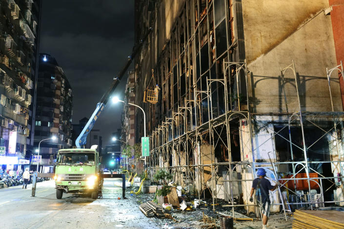 Workers break the glass windows of a building after a fire to prevent further hazard in Kaohsiung in southern Taiwan, Thursday, Oct. 14, 2021. Officials say at least 46 people were killed and over 40 injured after a fire broke out in a decades-old mixed commercial and residential building in the Taiwanese port city of Kaohsiunging. Neighborhood residents say the 13-story building was home to many poor, elderly and disabled people and it wasn't clear how many of the 120 units were occupied. (AP Photo/Huizhong Wu)