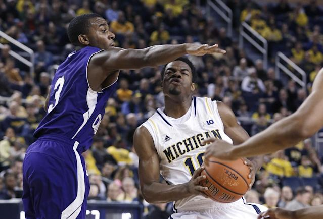 Michigan guard Derrick Walton Jr. (10) is defended by Holy Cross guard Justin Burrell (3) during the first half of an NCAA college basketball game in Ann Arbor, Mich., Saturday, Dec. 28, 2013. (AP Photo/Carlos Osorio)
