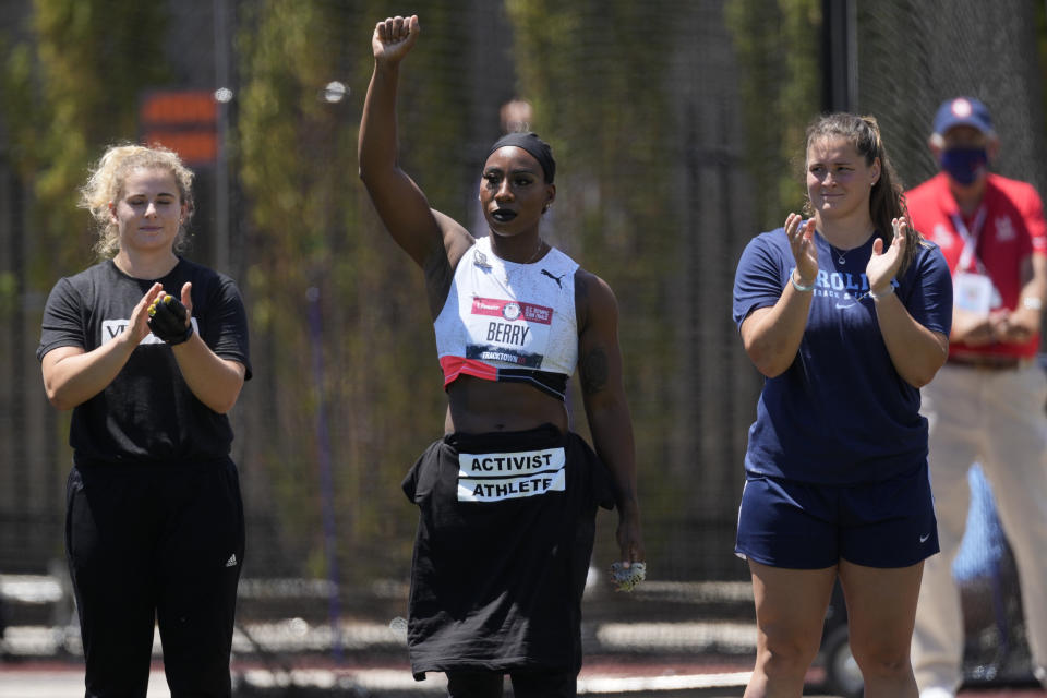 Gwendolyn Berry lifts her arm during introductions for the prelims of the women's hammer throw at the U.S. Olympic Track and Field Trials Thursday, June 24, 2021, in Eugene, Ore. (AP Photo/Ashley Landis)