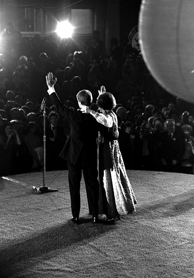 President and Mrs. Carter wave from the stage of the Visitor's Center in Washington where one of the seven inaugural balls was held, Thursday night, January 20, 1977. (AP Photo/stf)