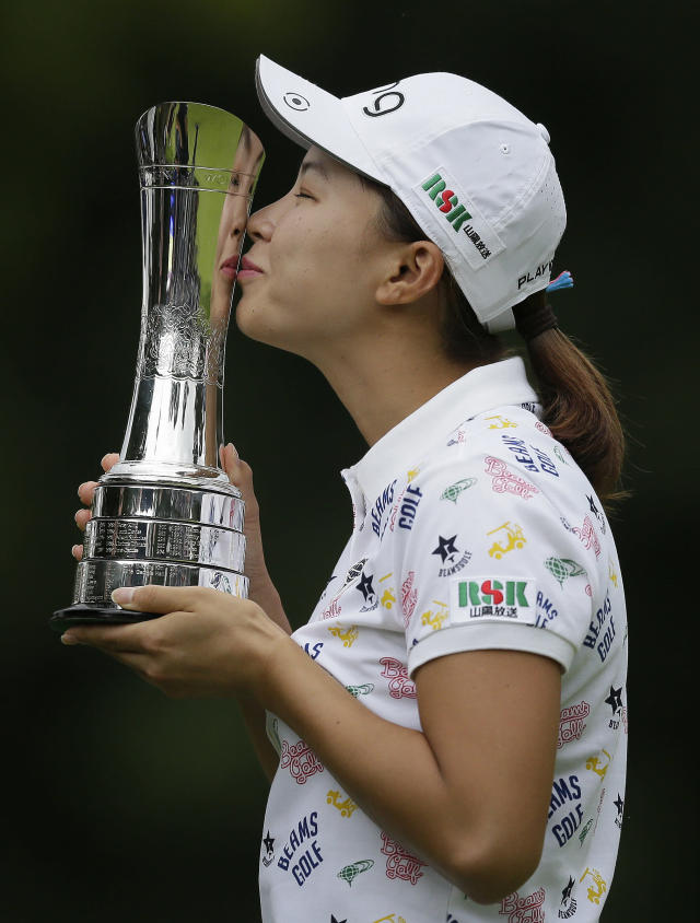 Japan's Hinako Shibuno kisses the trophy as she celebrates after winning the Women's British Open golf championship at Woburn Gold Club near near Milton Keynes, England, Sunday, Aug. 4, 2019. (AP Photo/Tim Ireland)