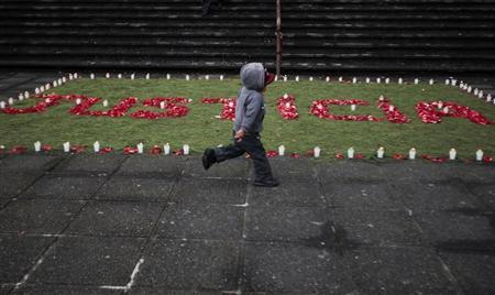 "A child runs past an arrangement of flowers and candles that reads: ""Justicia"" (or Justice) in front of the Supreme Court at Guatemala City"