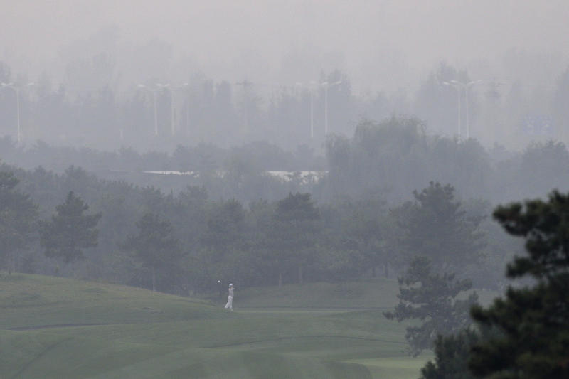 A golfer plays on the court on a hazy day at Pine Valley Golf Club on the outskirts of Beijing, China, Sunday, Oct. 6, 2013. Fog and pollution descended on northern China on Sunday, forcing international golf and tennis players to play in hazardous smog and leading to flight cancellations and road closures as millions of Chinese headed home from a national holiday. (AP Photo/Alexander F. Yuan)