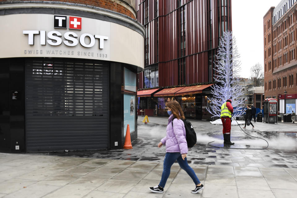 A woman wears a face mask as she walks past a closed shop, while a man cleans the pavement in Oxford Street, in London, Tuesday, Nov. 24, 2020. Haircuts, shopping trips and visits to the pub will be back on the agenda for millions of people when a four-week lockdown in England comes to an end next week, British Prime Minister Boris Johnson said Monday. (AP Photo/Alberto Pezzali)