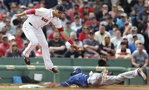 Boston Red Sox third baseman Will Middlebrooks comes down from getting a high throw too late to tag Toronto Blue Jays' Emilio Bonifacio stealing third during the sixth inning of an American League MLB baseball game at Fenway Park in Boston Sunday, May 12, 2013. (AP Photo/Winslow Townson)