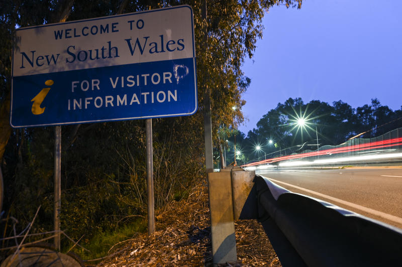 Cars cross the border from Victoria into New South Wales (NSW) in the NSW-Victoria border town of Albury, NSW.