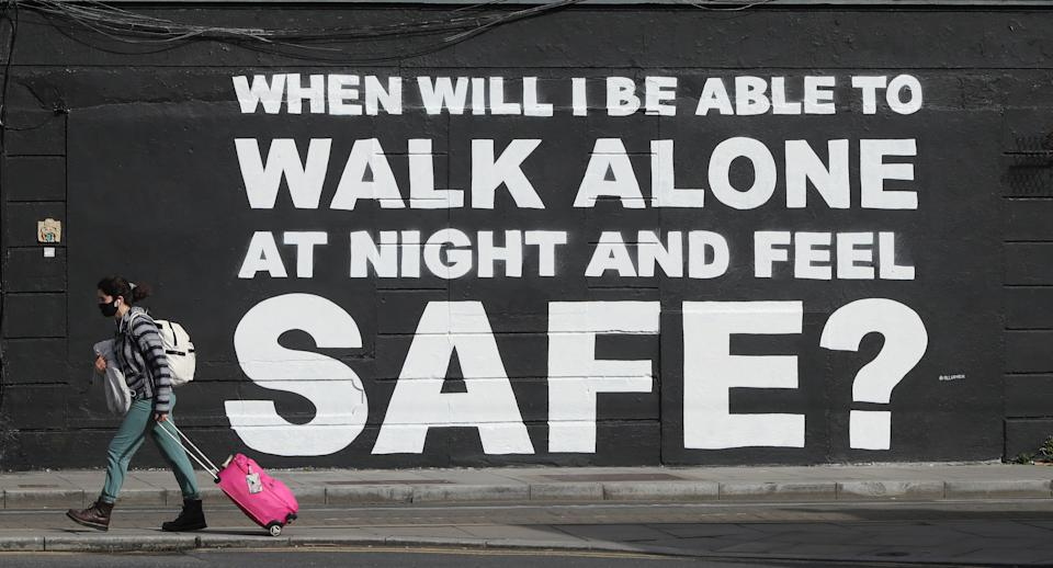 A member of the public walks past the latest mural by Irish artist Emmalene Blake in Dublin's city centre. The inscription 'When will I be able to walk alone at night and feel safe?' relates to violence against women in the wake of the death of Sarah Everard. Picture date: Monday March 29, 2021. (Photo by Niall Carson/PA Images via Getty Images)