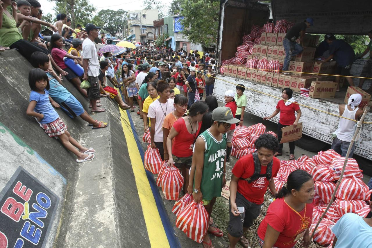 Residents queue up for relief goods being distributed by a non-government organization at Calumpit township, Bulacan province north of Manila, Philippines Tuesday Oct. 4, 2011. Floodwaters slowly receded in many parts of the northern Philippines after two typhoons that killed nearly 60 people, amid appeals for more boats to bring food and water to residents refusing to abandon inundated homes. (AP Photo/Bullit Marquez)