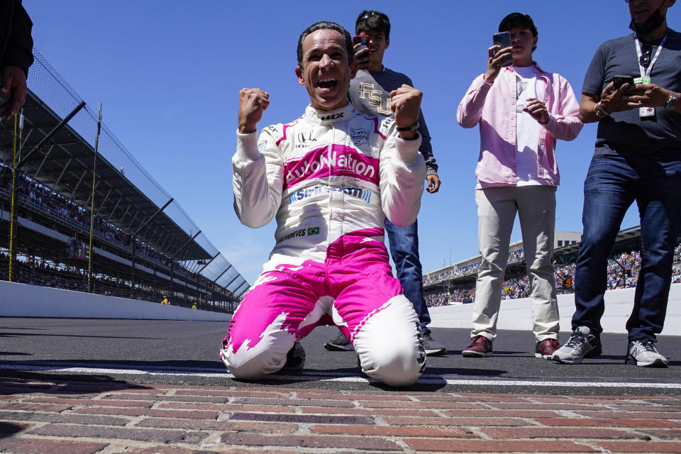 Helio Castroneves of Brazil celebrates on the yard of bricks at the start/finish line winning the Indianapolis 500 auto race at Indianapolis Motor Speedway in Indianapolis, Monday, May 31, 2021. (AP Photo/Paul Sancya)