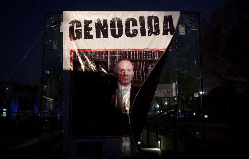 "A banner with a defaced picture of Mexico's President Felipe Calderon that reads in Spanish ""Genocide"" hangs on the covering of a stairway where it was placed by demonstrators protesting violence in Mexico City, Wednesday, Nov. 28, 2012.  Mexico will inaugurate a new president on Saturday, after Calderon's six-year militarized offensive against drug cartels. (AP Photo/Alexandre Meneghini)"