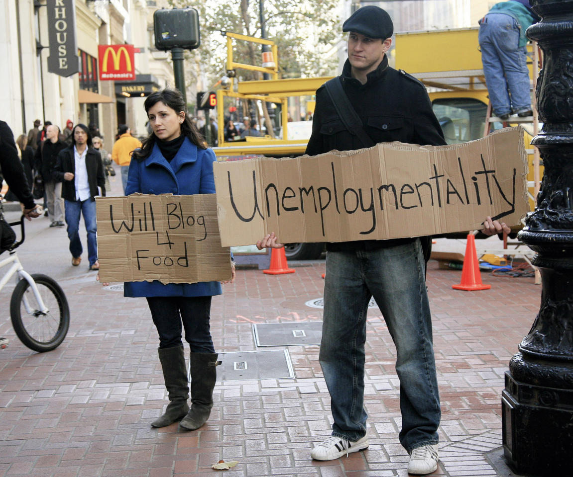 "Tania Khadder (L), 29, and John Henion, 32, both unemployed online journalists, hold signs announcing a new blog called ""unemploymentality.com"" along Market Street in San Francisco, California December 9, 2008. Both have been laid off from their media jobs and are starting the blog to document the current economic situation from their point of view, and others in similar situations. REUTERS/Robert Galbraith  (UNITED STATES)"