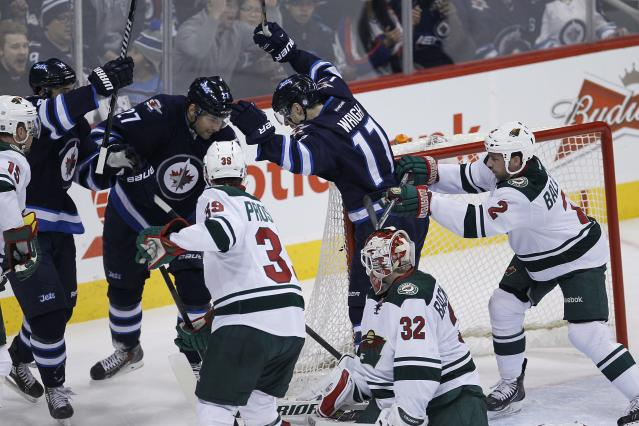 Winnipeg Jets' Anthony Peluso (14), Eric Tangradi (27) and James Wright (17) celebrate Dustin Byfuglien's (not shown) goal against Minnesota Wild's Nate Prosser (39), goaltender Niklas Backstrom (32) and Keith Ballard (2) during first-period NHL hockey game action in Winnipeg, Manitoba, Friday, Dec. 27, 2013. (AP Photo/The Canadian Press, John Woods)
