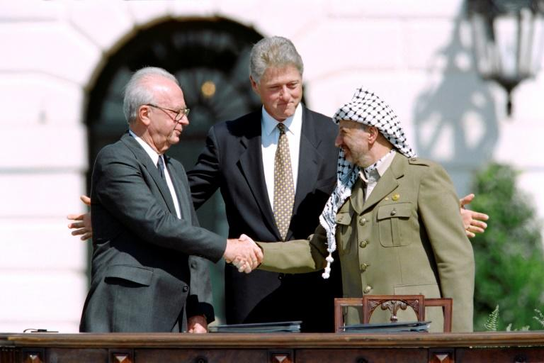 Then US President Bill Clinton (C) stands between PLO leader Yasser Arafat (R) and Israeli Prime Minister Yitzhak Rabin (L) as they shake hands on September 13, 1993 at the White House after signing the Oslo Accords
