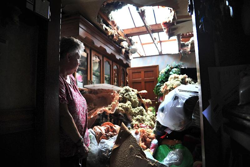 Faye Busby looks over her living room after a tornado ripped part of the roof off of her home in Graysville, Ala.,Tuesday, April 29, 2014. A strong line of tornado-producing storms made its way across the southeast Monday causing damage in the area.(AP Photo/AL.com, Tamika Moore)