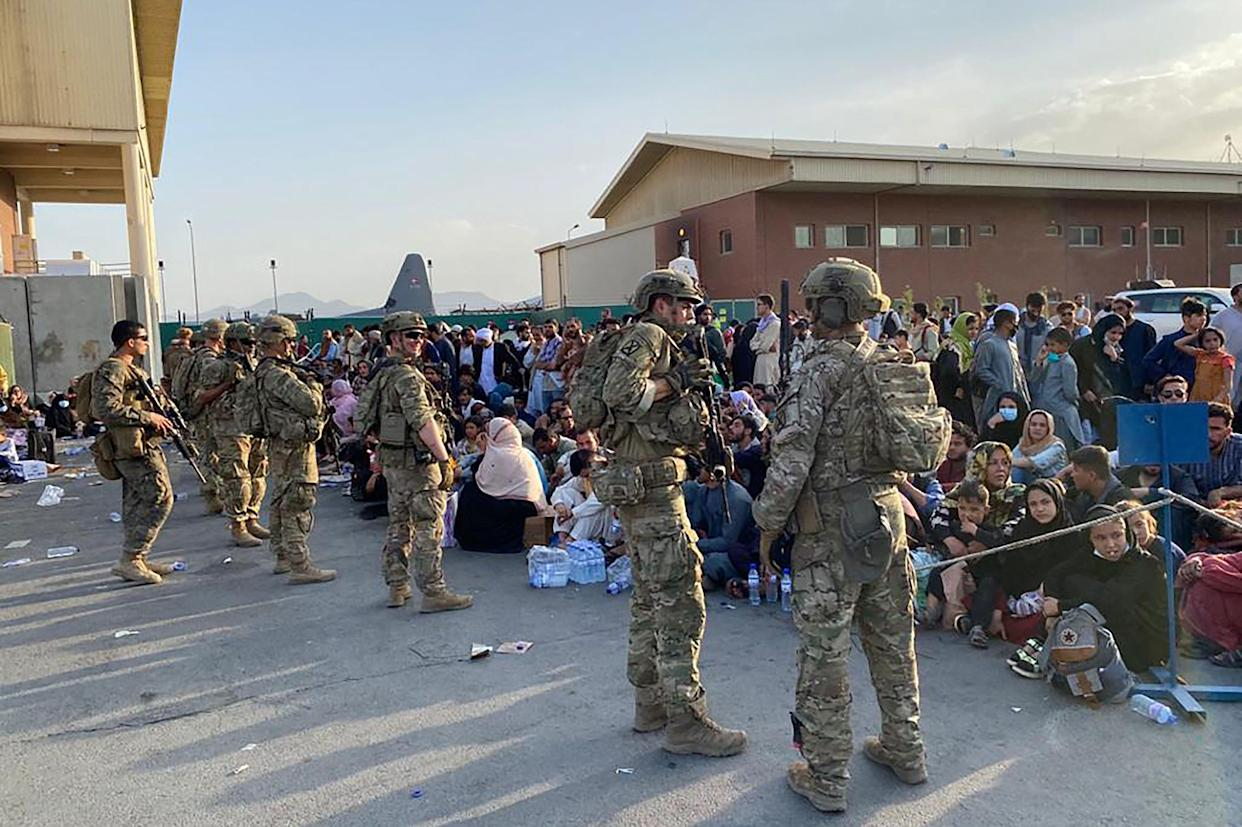 US soldiers stand guard as Afghan people wait to board a US military aircraft  to leave Afghanistan, at the military airport in Kabul on August 19, 2021 after Taliban's military takeover of Afghanistan. (Photo by Shakib RAHMANI / AFP) (Photo by SHAKIB RAHMANI/AFP via Getty Images)