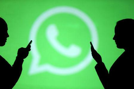 Silhouettes of mobile users are seen next to a screen projection of Whatsapp logo in this picture illustration