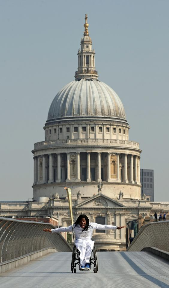 In this photo provided by LOCOG, torchbearer Ade Adepitan carries the Olympic Flame on Millennium Bridge during Day 69 of the London 2012 Olympic Torch Relay, Thursday, July 26, 2012, in London. (AP Photo/LOCOG, Chris Radburn)