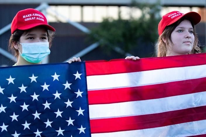Two young people wearing red Make America Great Again hats hold up a U.S. flag