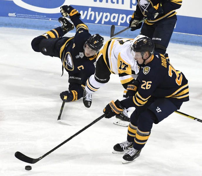 Buffalo Sabres center Jack Eichel (9) falls to the ice as Pittsburgh Penguins' Bryan Rust (17) goes after a puck controlled by Sabres' Rasmus Dahlin (26) during t an NHL preseason hockey game, Monday, Sept. 16, 2019, in State College, Pa. (AP Photo/John Beale)