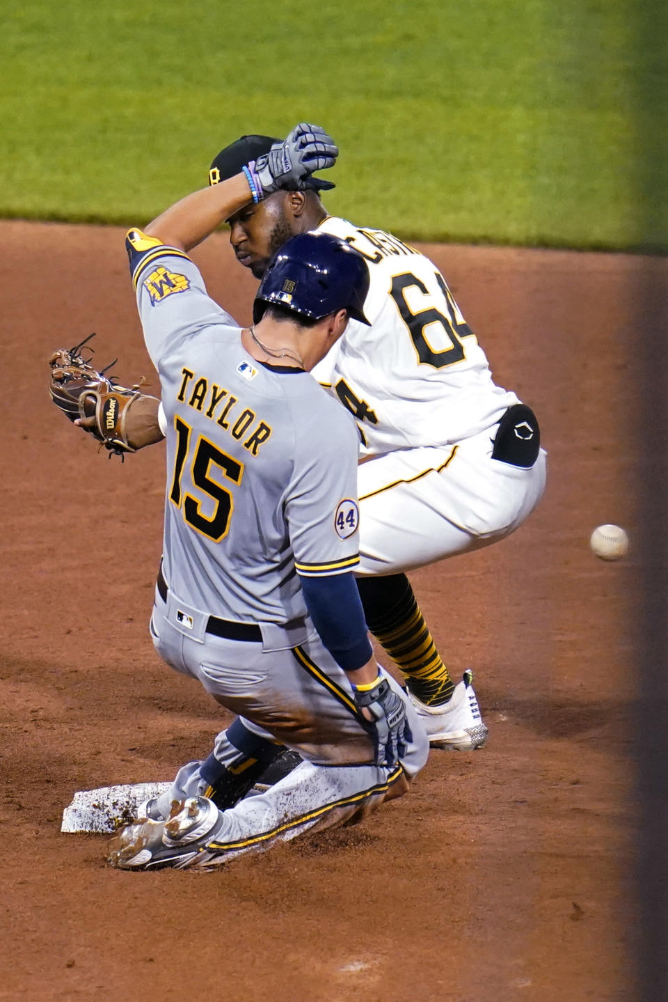 Milwaukee Brewers' Tyrone Taylor (15) slides safely into second with an RBI double as the relay throw gets past Pittsburgh Pirates second baseman Rodolfo Castro during the sixth inning of a baseball game in Pittsburgh, Thursday, July 29, 2021. (AP Photo/Gene J. Puskar)