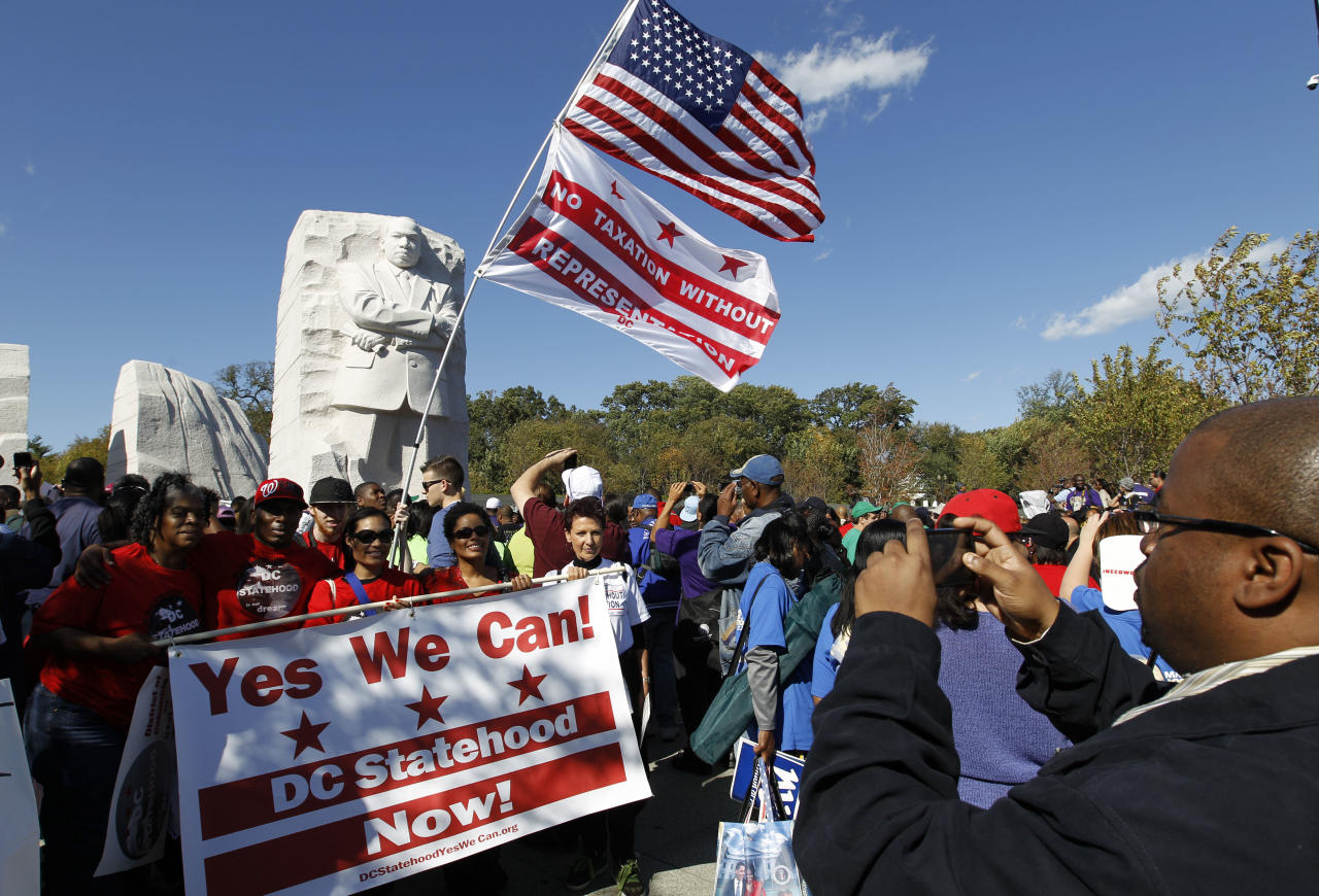 Demonstrators pose for a photo near the new Martin Luther King Jr. Memorial during a rally and march of thousands in Washington Saturday, Oct. 15, 2011. Civic leaders, led by the Rev. Al Sharpton, rallied for easier access to jobs, but speakers used the platform for causes as varied as condemning voter identification laws and last month's execution of Troy Davis in Georgia. (AP Photo/Jose Luis Magana)