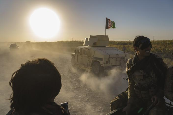 Two people are seen, dark against the sun's glare, as military vehicles kick up clouds of dust on a rocky road.