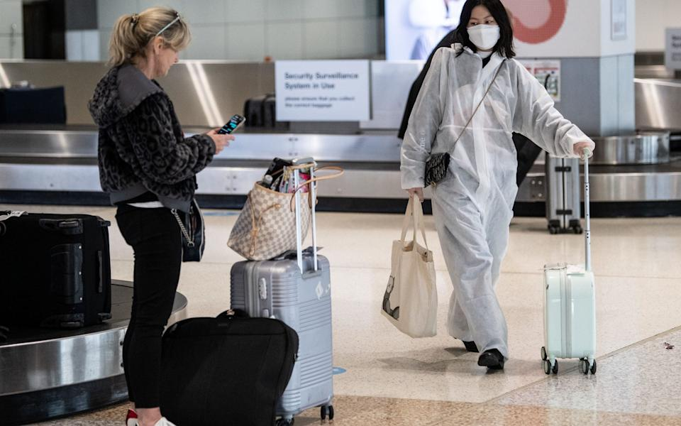 A passenger wearing a protective suit and mask at Sydney Airport - JAMES GOURLEY/EPA-EFE/Shutterstock