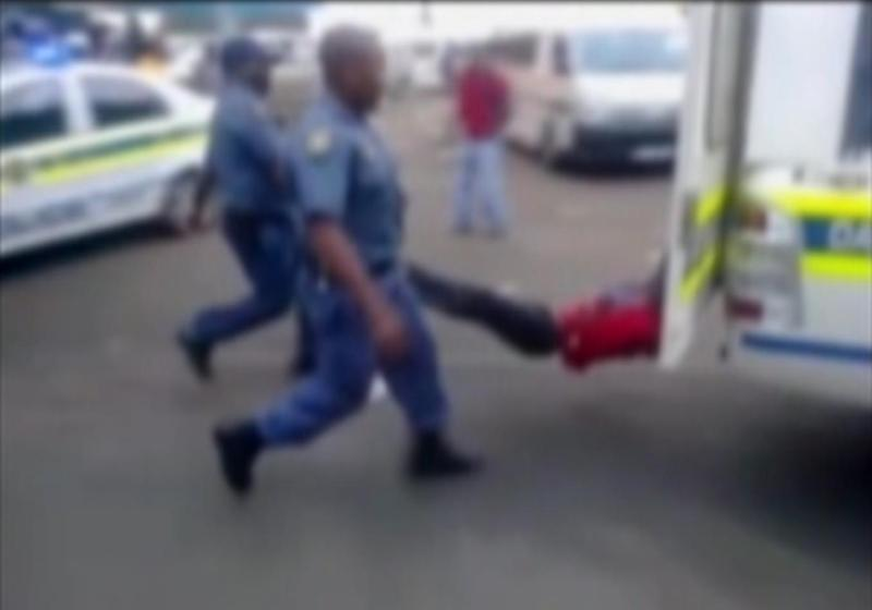 In this still frame from TV and courtesy of South African Daily Sun newspaper, showing a South African man with his hands tethered behind a police vehicle and being dragged behind as police hold his legs up and the vehicle apparently drives off, east of Johannesburg Tuesday Feb. 26, 2013. The man died of his injuries. In video filmed on a mobile phone, uniformed police are seen trying to subdue the man, then tethering him to the back of a police vehicle which drives off, watched by a large crowd. Moses Dlamini of the Independent Police Investigative Directorate said early Thursday Feb. 28 2013 on ENCA TV network that his service has opened a murder probe. (AP Photo/The Daily Sun) TV OUT