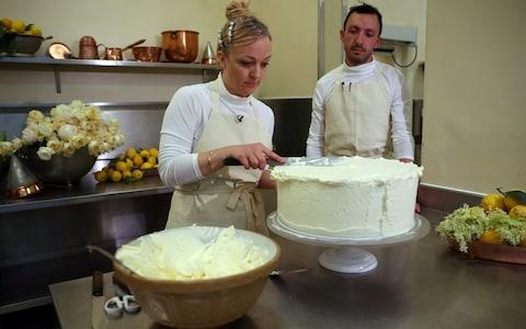 Claire Ptak, owner of Violet Bakery in Hackney, east London, and head baker Izaak Adams put finishing touches to the cake - Credit: HANNAH MCKAY /Reuters