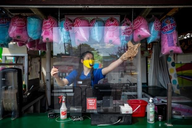 A worker sanitizes a protective screen at a cotton candy concession stand before the opening of Playland at the PNE in Vancouver, British Columbia on Friday, July 10, 2020.