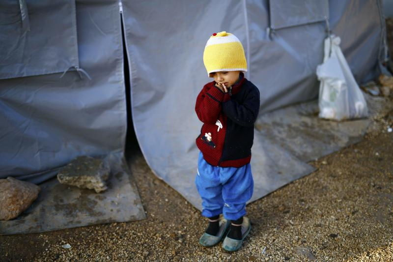 A Kurdish refugee child from the Syrian town of Kobani stands outside a tent in a camp in the southeastern town of Suruc