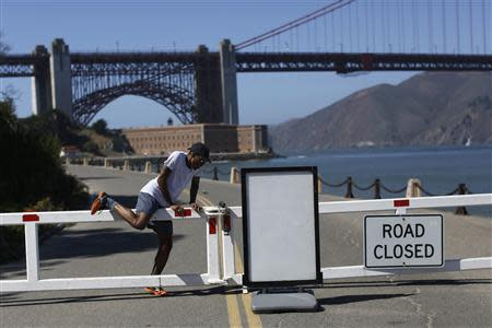 A runner climbs over a road gate leading to Fort Point National Historic Site, which has been closed due to the federal government shutdown, in San Francisco, California October 2, 2013. REUTERS/Stephen Lam