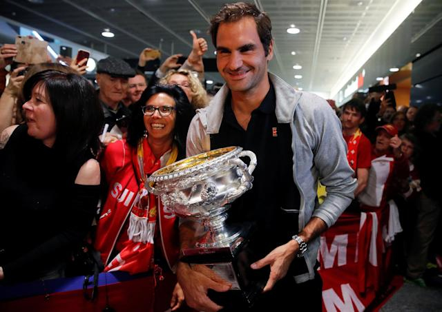 Switzerland's Roger Federer holds his Australian Open trophy as he is welcomed by fans upon his arrival at Zurich Airport, Switzerland January 30, 2018. REUTERS/Arnd Wiegmann -